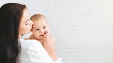 Mother Kiss Child, Baby Rests On Mom Shoulder