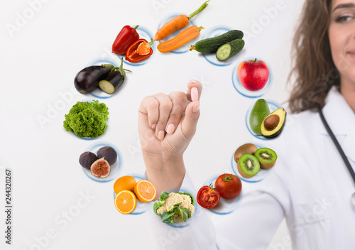 Hand of nutritionist doctor showing pill on symbols fruits Canvas Print