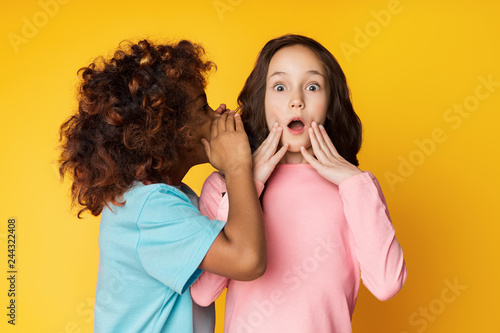 Photo  Girl telling secret to her friend, whispering in ear