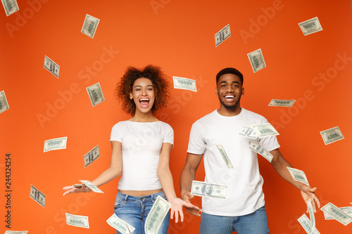 Fototapeta Young black couple standing under money banknotes shower obraz