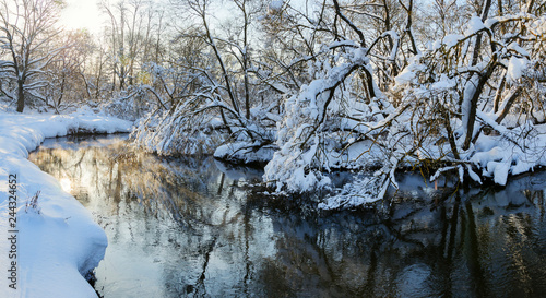 Foto auf Gartenposter Fluss Wintertime.Amazing winter scenery.Quiet stream of water.Landscape with flowing river.Snow-covered trees.Beautiful christmas scene.Sun shining and illuminates the branches.Sunny frosty morning.
