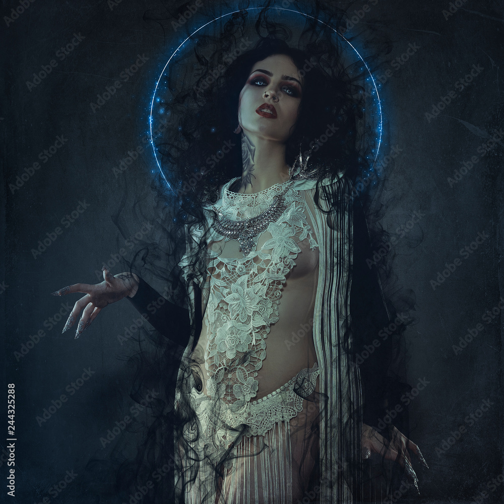Fototapeta vampire, demonic woman dressed in white lace and silver jewelry. has fangs and thick brown hair