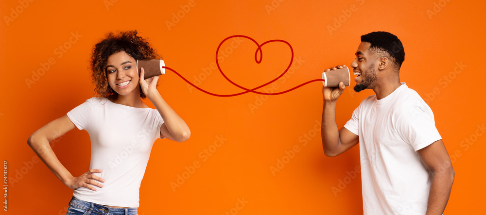 Fototapety, obrazy: Young black couple with can phone on orange background
