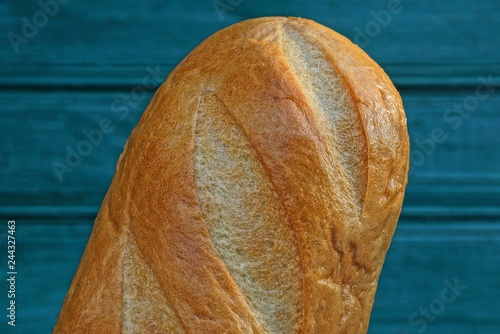 Fotografie, Obraz  a large piece of brown loaf against a green wall