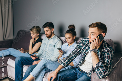 Photo  handsome fair-haired guy is talki g on the phone while his fiends are surfing the Net