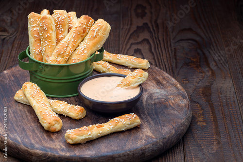 Fotografía  Homemade savory bread sticks with cheese and sesame in a basket, served with sau