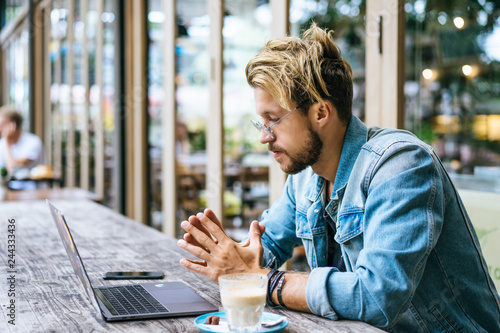Fototapety, obrazy: young attractive business man in a cafe works for a laptop, drinks coffee.