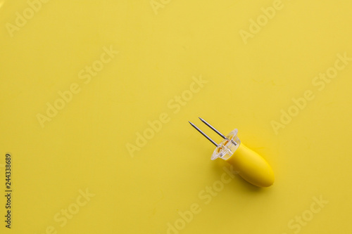 Yellow corn holder on yellow background table top