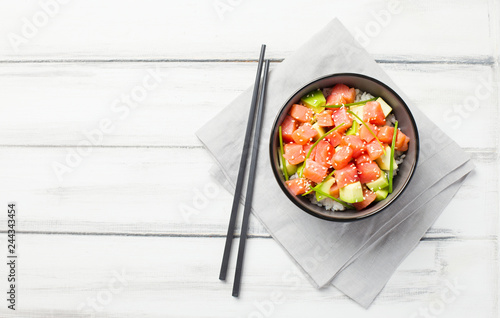 Stampa su Tela Poke with diced raw salmon and avocado decorated with green onions and sesame seeds in bowl with chopsticks