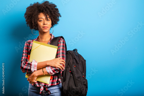 young african student with backpack on the back on blue background Fototapeta