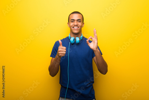 Fototapeta African american man with blue t-shirt on yellow background showing ok sign with