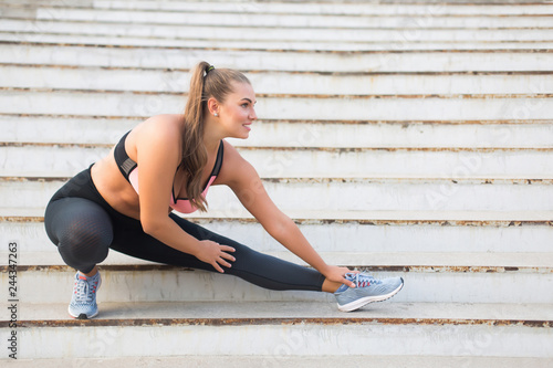 Foto  Joyful plus size girl in sporty top and leggings happily stretching on stairs wh