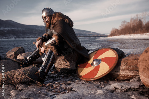 Medieval Scandinavian warrior Viking in full outfit on shore of winter sea Canvas Print