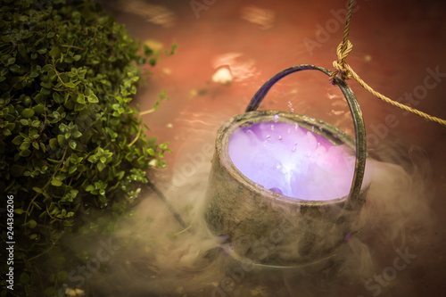 Cauldron with purple magic boiling potion or witching toxic poison
