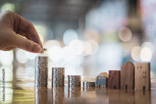 Wallpaper Mural Hand choosing row of coin money on wood table and mini wood house, selective focus, Planning to buy property