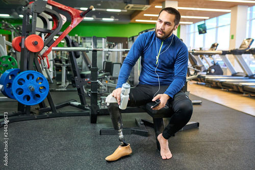 Photo Young handsome sportsman with amputee leg sitting in gym with bottle of water an