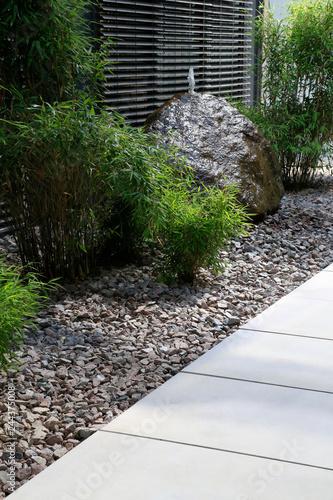 Moderner Gartenbau: Gehweg aus Betonplatten und Grünpflanzen im  Schotterbeet vor einem Felsen mit Wasserfontäne