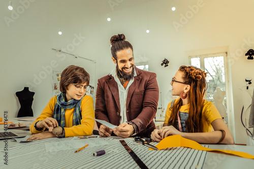 Fotografija  Bearded fashion designer giving master class for children