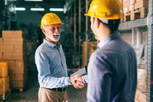 Two businessmen shaking hands for successful business while standing in warehouse.
