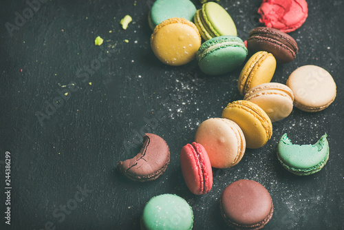 Photographie Sweet colorful French macaroon cookies variety with sugar powder over black back