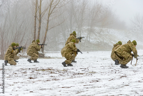 Photo A combat squad in camouflage with a weapon goes on the offensive in winter