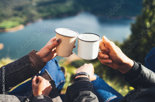 Canvas Print lovers couple hold in hands mug of hot drink, enjoy together of sun flare mounta