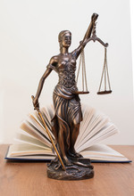 Statue Of Justice On Wooden Table Against The Background Of An Open Book