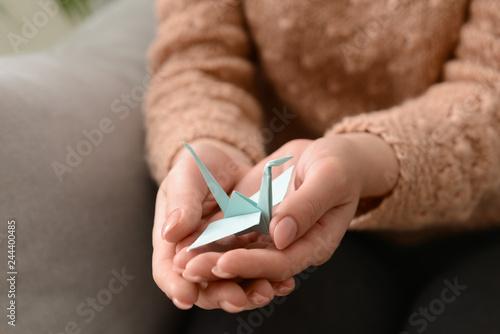 Fototapeta  Young woman holding origami bird, closeup