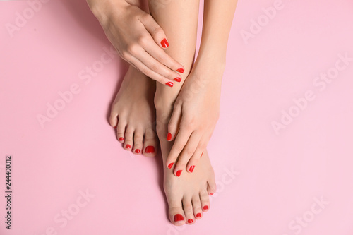Foto op Canvas Pedicure Young woman with beautiful pedicure on color background