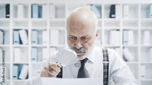 Fotografía  Corporate businessman checking paperwork with a magnifier