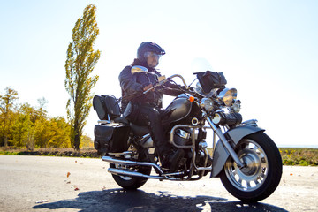 Motorcycle Driver Riding Custom Chopper Bike on Autumn highway. Adventure Concept.