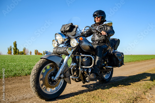 Foto auf Leinwand Motorsport Motorcycle Driver Riding Custom Chopper Bike on Autumn Dirt Road in the Green Field. Adventure Concept.