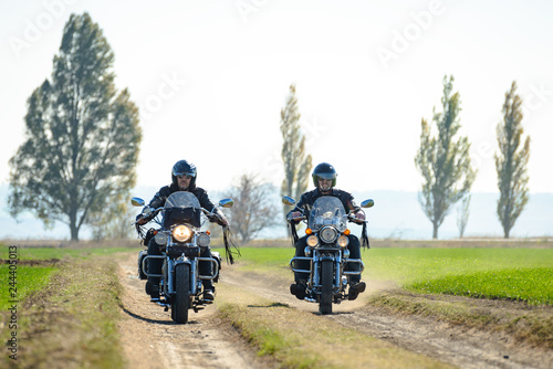 Two Motorcycle Drivers Riding Custom Chopper Bikes on an Autumn Dirt Road in the Green Field. Adventure Concept.