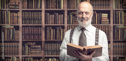 Fotografie, Obraz  Academic professor in the library holding a book