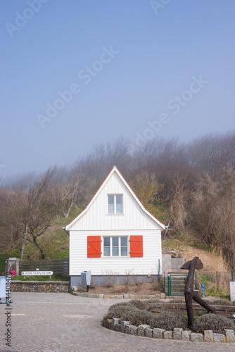 Fotografie, Obraz  Kleines Haus, Holzfassade weiß, rote Fensterläden aus Holz, Gebüsch von Windflüc