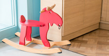 Red Rocking Horse Toy For Kid In Home Living Room, Cheerful Riding Stuff For Children Playing On The Wooden Floor In Nursery, Child Furniture Background Concept With Copy Space