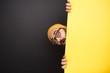 Leinwandbild Motiv Funny man peeking out from behind yellow banner
