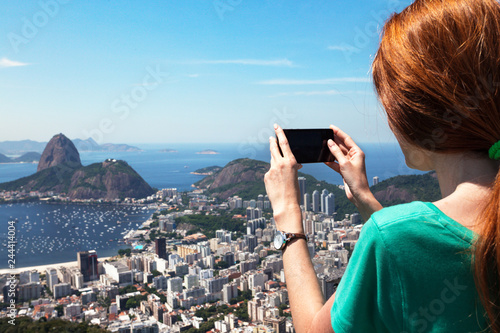 girl tourist takes a picture of Rio landscape with smartphone