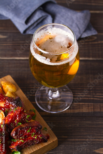 Tuinposter Bier / Cider Glass of beer and grilled pork spare ribs with fry, tasty snack to beer. Beer and food concept. Ale and meat