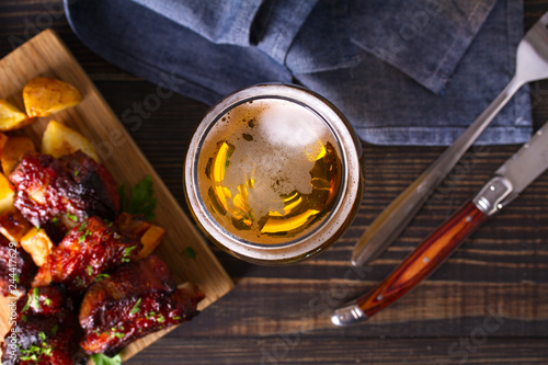 Tuinposter Bier / Cider Glass of beer and grilled pork spare ribs with fry, tasty snack to beer. Beer and food concept. Ale and meat. View from above, top studio shot