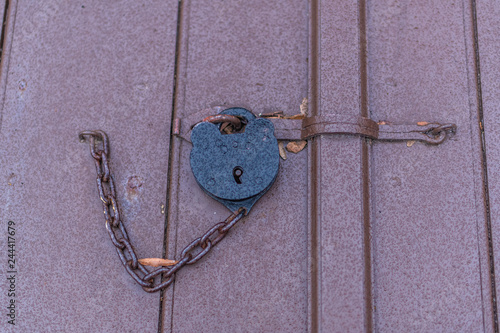 Fotografie, Obraz  An antique colonial style padlock holding open doors in Colonial Williamsburg in