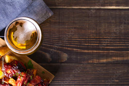 Photo sur Aluminium Biere, Cidre Glass of beer and grilled pork spare ribs with fry, tasty snack to beer. Beer and food concept. Ale and meat. View from above, top studio shot, copy space