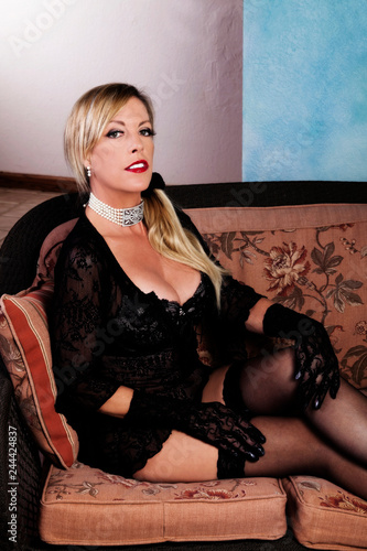 Fotografie, Obraz  Older Caucasian Woman Sitting On Couch In Black Lacy Lingerie