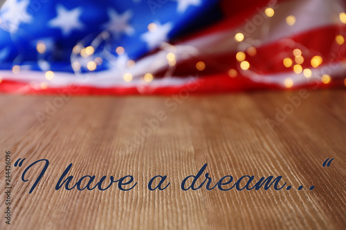 Photo  Blurred American flag and garland on wooden table. Space for text