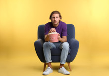 Emotional Man With Popcorn Sitting In Armchair During Cinema Show On Color Background