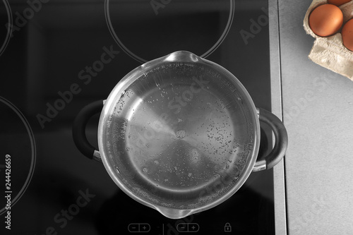 Valokuva Pot with boiling water on electric stove in kitchen, top view