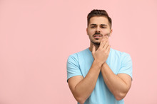 Young Man Suffering From Strong Tooth Pain On Color Background, Space For Text