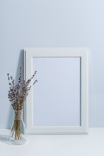 Mock Up White Frame And Lavender On Book Shelf Or Desk. White Colors. White-blue Colors. Minimalistic Concept.