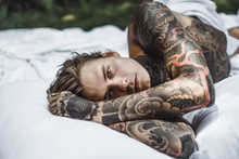 Young Handsome Tattooed Man Laying In Bed In The Open Air Outdoors In The Garden.