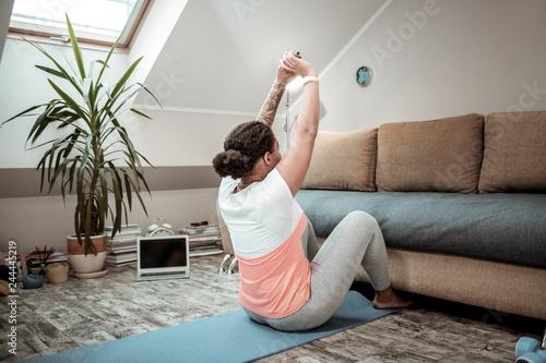 Fotografija  Dark-haired woman raising her hands while swinging press